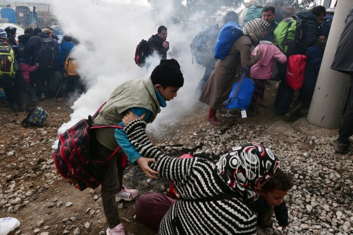 A woman holds her children as tear gas is dispersed (POLITICO Europe).