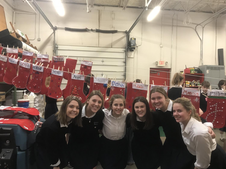 Wini Bettenburg, Maddie Mork, Rachel Coss, Sara Commers, Sadie Grunau, and Nicole Bauman in front of completed  Christmas stockings.